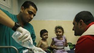 Crianças esperam atendimento em hospital de Gaza depois da retomada dos ataques