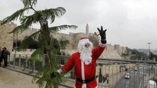 Homem vestido de Papai Noel passeia em torno de muro que protege a cidade antiga de Jerusalém.