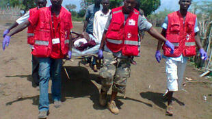 Members of the Kenya Red Cross carry an injured man after an attack in his village at Tana River district, 21 December