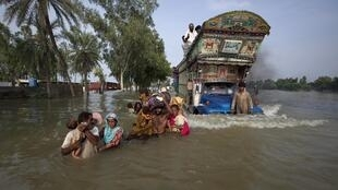 A family wades through flood waters in Pakistan's Muzaffargarh district of Punjab province