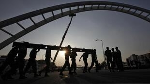 Indian soldiers rebuild a bridge that collapsed during the Commonwealth Games