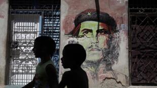 """Crianças cubanas passam diante de uma imagem do """"Che"""" em Havana. Um navio cargueiro americano deve chegar ao porto da cidade nesta sexta-feira (13)."""