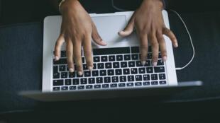 Main de femme tapant sur le clavier d'un ordinateur portable.