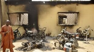 A man walks through the ruins of a zonal police headquarters after a bomb attack in Nigeria's northern city of Kano
