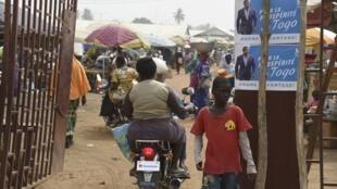 Vue d'un marché de Lomé, avec à l'entrée des affiches électorales du canidat-président Faure Gnassingbé le 14 février 2020.