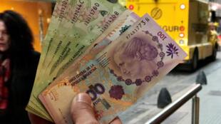 A Buenos Aires, un homme brandit une liasse de la monnaie argentine, le peso.