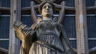 Une statue représentant la justice se dresse au-dessus de l'entrée principale du palais de justice du district de Wedding à Berlin le 24 janvier 2020.