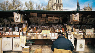 Bouquinistes sell their wares on both banks of the Seine out of traditional bottle green wooden boxes