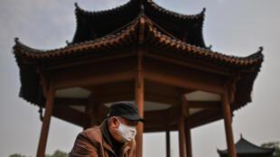 Un hombre con mascarilla visita el Parque Hanyang Lianhuahu de la ciudad china de Wuhan el 3 de abril de 2020