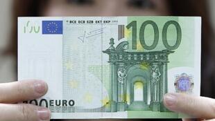 Một nhân viên ngân hàng châu Á giơ cao tờ 100 euros