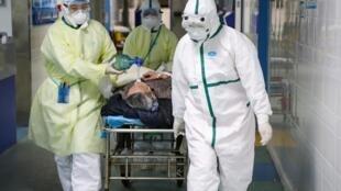 中国湖北省武汉市蔡甸区的医务工作者在救护新冠病毒患者 摄于2020年2月6日  Medical workers move a patient at an isolated ward of a hospital in Caidian district following an outbreak of the novel coronavirus in Wuhan, Hubei province, China February 6, 2020.