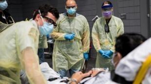 Des soldats affectés au Javits New York Medical Station effectuent des procédures d'enregistrement sur un patient atteint de coronavirus avec des travailleurs d'urgence locaux dans la baie médicale de l'établissement à New York City, États-Unis,