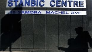 Men cast shadows as they walk past a banking centre in the capital Harare, 3 July, 2012