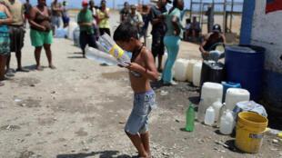 Un niño transporta agua hasta una planta de desalinisación. La Guaira, Venezuela, 13 de marzo de 2019.
