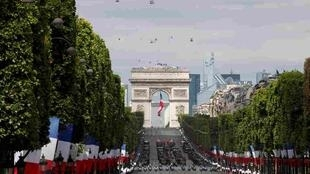Troops march down the Champs-Elysees avenue during the traditional Bastille Day military parade in Paris, France, July 14, 2015. In the background, the Arc de Triomphe.