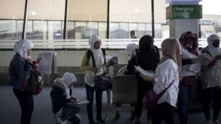 Trabalhadoras filipinas chegam ao Aeroporto Internacional de Manila em 18 de fevereiro de 2018. Depois de um assassinato de uma empregada filipina no Kuwait, muitas relatam abusos e dificuldades.
