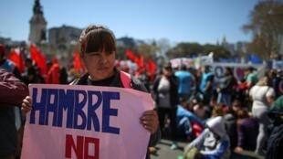Une manifestante, avec une pancarte « Non à la faim », lors d'une marche contre les mesures économiques du président Mauricio Macri, à Buenos Aires, le 12 septembre 2019.