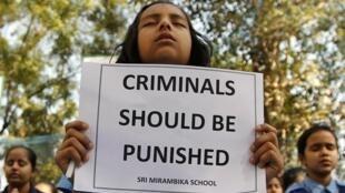 Jovem manifestante indiana pede punição aos criminosos que estupraram e mataram uma estudante de 23 anos em Nova Délhi, no último sábado.