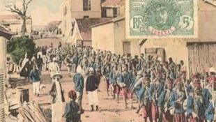 Carte postale ancienne montrant un défilé de tirailleurs à Dakar.