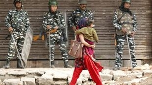 A woman carrying a child walks past security forces in a riot affected area after clashes erupted between people demonstrating for and against a new citizenship law in New Delhi, India, February 26, 2020.