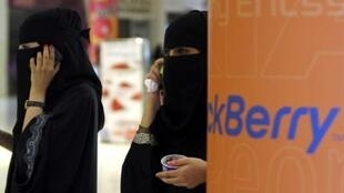 Veiled Saudi women talk on their BlackBerry phones at a shopping mall in Riyadh