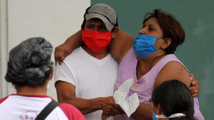 A man helps a sick woman enter a hospital in Guayaquil, Ecuador on April 1, 2020