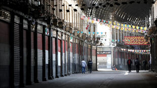 People walk through the shuttered century-old covered bazaar of Hamidiya in Syria's capital Damascus