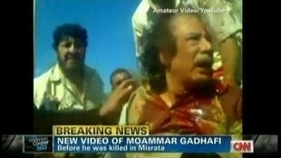 Moamer Kadhafi just after his capture, alive, bleeding from a head wound...