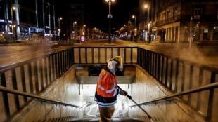 Un travailleur portant une combinaison de protection nettoie et désinfecte un escalier d'un passage souterrain pour empêcher la propagation du Covid-19, au centre-ville de Budapest, le 26 mars 2020, où les rues sont désertes.