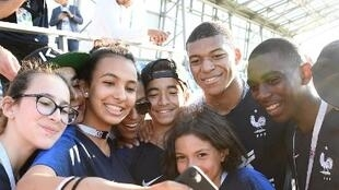 France's forward Kylian Mbappe (2R) poses with young fans from Paris' commune of Bondy at the end of a training session in Istra, west of Moscow on June 27, 2018, during the Russia 2018 World Cup football tournament.