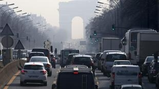 Rush hour traffic at Paris's Arc de Triomphe which is seen through a small-particle haze on 13 March 2014.