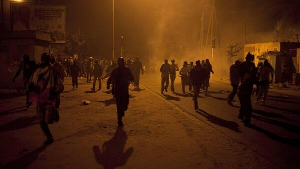 Anti-government protestors run from tear gas in Dakar