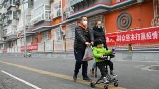 Tres personas caminan por Pekín protegidas con mascarillas el 13 de febrero de 2020