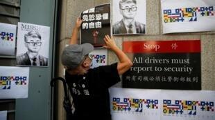 Một người biểu tình dán một tấm poster trên tường tổng lãnh sự quán Anh Quốc ở Hồng Kông, ngay cạnh ảnh của Trịnh Văn Kiệt (Simon Cheng), nhân viên tòa lãnh sự bị Trung Quốc bắt giữ hôm 09/08. Ảnh chụp ngày 21/08/2019.