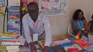 Le responsable des éditions Thanks (Yaoundé) qui classe ses livres édités en langues patrimoniales.