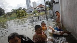 Boys play in the water in a flooded slum as floods advance into central Bangkok 26 October, 2011.