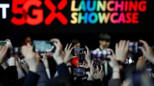 Clientes fotografam o lançamento do serviço 5G de SK Telecom em Seul.