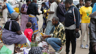 Kenyan activist Boniface Mwangi (C) talks to a street hawker in Nairobi during his campaign ahead of the August election