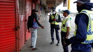 Des policiers sud-africains tentent de faire respecter les mesures de confinement à Durban le 27 mars 2020.