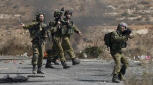 Os soldados israelitas durante os confrontos com os manifestantes palestinianos junto às colónias de Bet El, na Cisjordânia, a 5 de Outubro de 2015
