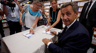 Former French president Nicolas Sarkozy autographs his book in which he annouced his intention to run for presidency in 2017, in Le Touquet, France August 27, 2016.