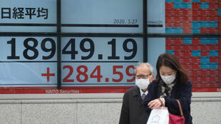 Unos peatones con mascarilla pasan por delante de una pantalla con las cotizaciones de la Bolsa de Tokio el 27 de marzo de 2020 en la capital japonesa