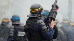 Полицейский пускает гранату со слезоточивым газом во время акции «желтых жилетов» на площади Италии 16 ноября