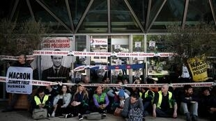 """Environmental activists block the entrance to the headquarters of French oil giant Total during a """"civil disobedience action"""" to urge world leaders to act against climate change, in La Defense near Paris, France, April 19, 2019."""