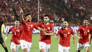 Trézéguet celebrates with his Egypt teammates after scoring against Zimbabwe.