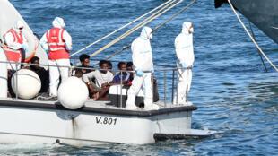 Menores desacompanhados deixam o navio Open Arms, em Lampedusa.