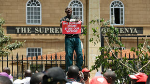 A supporter of Kenya's President Uhuru Kenyatta carries a placard as they demonstrate outside the Supreme Court in Nairobi on 19 September, 2017.
