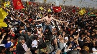 Demonstrators hold Kurdish flags with portraits of the jailed PKK leader Abdullah Ocalan, 21 March