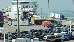 Trucks leave a ferry from Dover while passengers cars queue at the Calais harbour