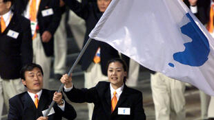 Vận động viên Bắc Triều Tiên Jang Choo Pak (T) và Hàn Quốc  Eun-Soon Chung mang cờ với biểu tượng thống nhất bán đảo trong buổi diễn hành khai mạc Thế Vận Sydney, Úc, 15/09/2000.